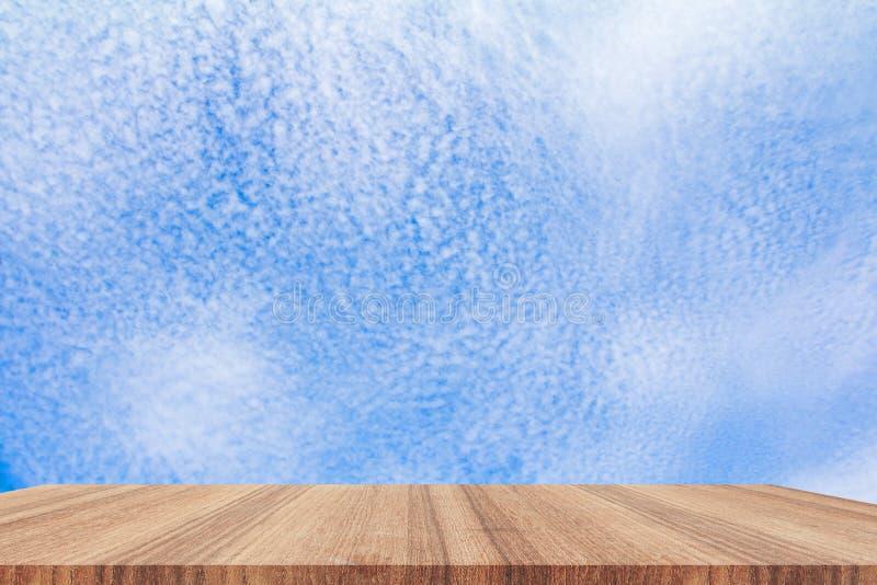 Deja de lado el top de madera del piso vacío con el fondo vivo de la nube del cielo azul fotografía de archivo