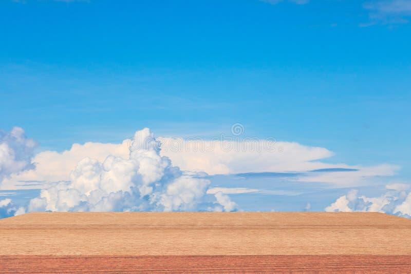 Deja de lado el top de madera del piso vacío con el fondo vivo de la nube del cielo azul foto de archivo
