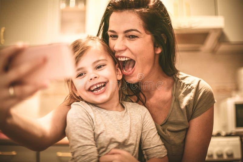 Deja para tomar un autorretrato Niña con la madre fotografía de archivo libre de regalías