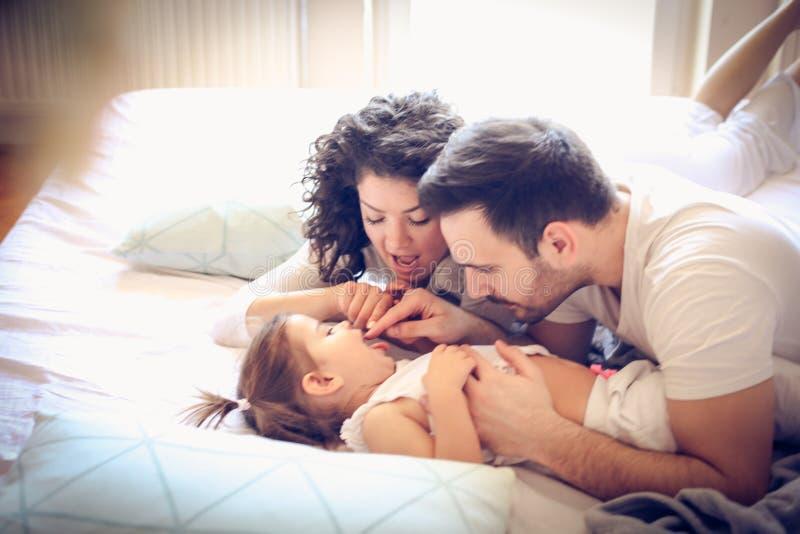 Dejado contamos sus dientes Padres jovenes con su niña fotografía de archivo libre de regalías