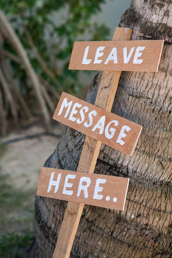Deje el lebel de madera del mensaje aquí en jardín fotos de archivo