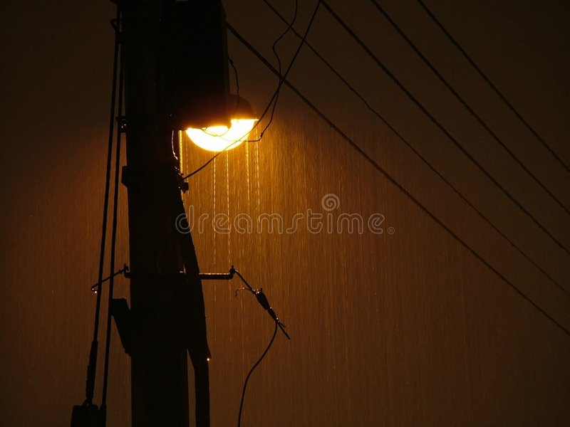 Dejected. A lamp pole in the rain at night stock image