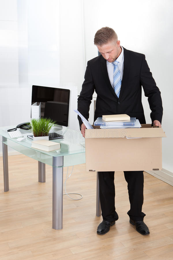 Dejected businessman made redundant. Or fired carrying a cardboard box full of his personal belongings with his head low as he leaves his office stock photos
