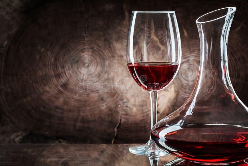 Dekanter und Weinglas mit Rotwein in sehr naher Nähe auf Holzboden lizenzfreies stockfoto