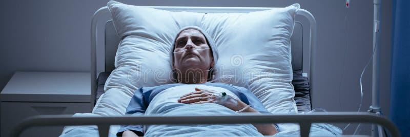 Dekkingsfoto van een eenzame, zieke vrouw die op een het ziekenhuisbed liggen met stock fotografie
