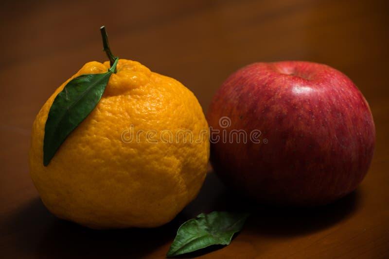 Dekopon en japansk organisk apelsin och ett rött äpple på träbaksidan royaltyfri fotografi