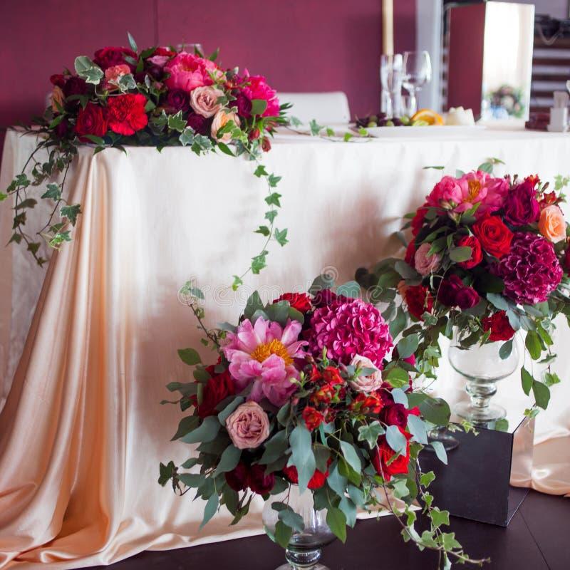 Dekor av nygifta personerna Siden- borddukar, röda blommor arkivfoton