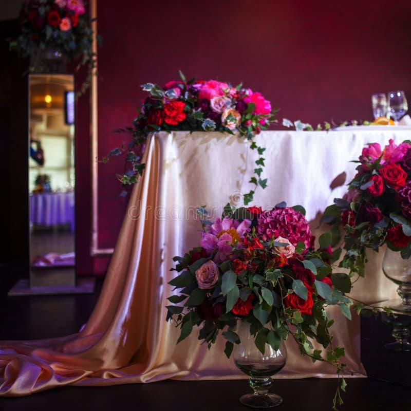 Dekor av nygifta personerna Siden- borddukar, röda blommor royaltyfri fotografi