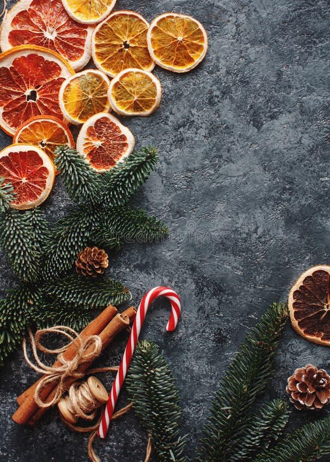 Dekor för lägenhet för jul eller för nytt år lekmanna- hem-, torra apelsiner, kanel, godisar och granfilialer på konkret bakgrund arkivbilder