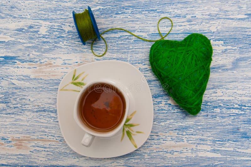 Dekor für Valentinsgruß ` s Tagesherz von grünen Threads auf einem hölzernen Hintergrund mit einer Tasse Tee und Kekse stockfotografie
