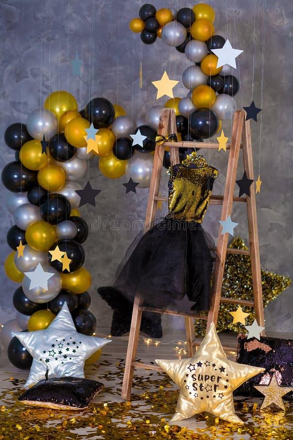 Dekoracja złota partyjna suknia z skórzanej kurtki obwieszeniem na drewnianym wieszaku w świetlicowych pracownianych dekoracjach obrazy royalty free