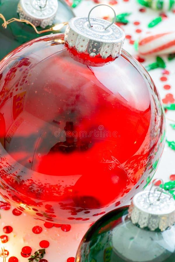 Dekoracja z czerwony fluid wypełniającymi bożymi narodzeniami ornamentuje piłkę i dwa zielenieją wypełniać ornament piłki otaczać fotografia royalty free