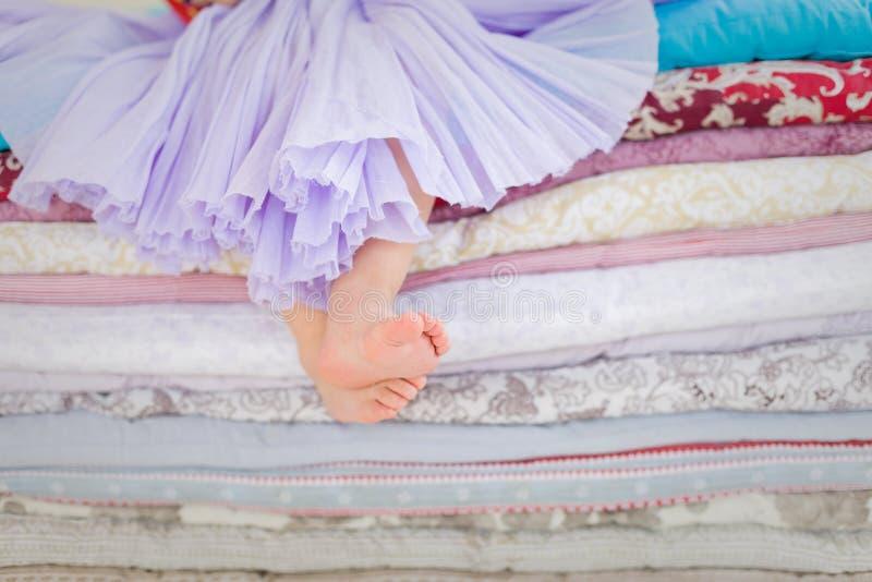Dekoracje dla bajki Princess i grochu Dziewczynka siedzi na stosie koc i materac z nagimi ciekami obrazy royalty free