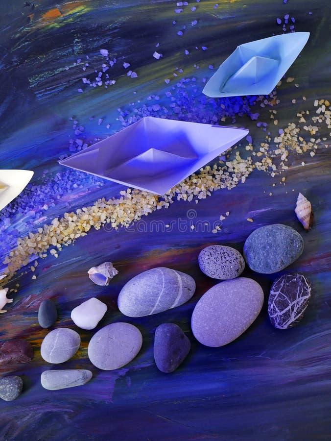 Dekoracyjna skład instalacja - gładkie morze kamieni, morze soli, skorup, rozgwiazdy i papieru łodzie na błękitnym tle, zdjęcia stock