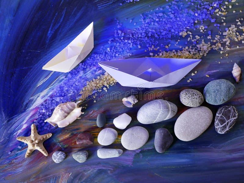 Dekoracyjna skład instalacja - gładkie morze kamieni, morze soli, skorup, rozgwiazdy i papieru łodzie na błękitnym tle, zdjęcia royalty free