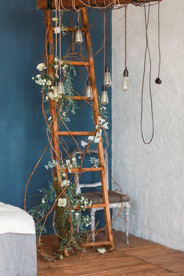 Dekoracyjne antykwarskie Edison stylu żarówki przeciw drewnianemu drabinowemu tłu światła na tle błękit ściana fotografia royalty free