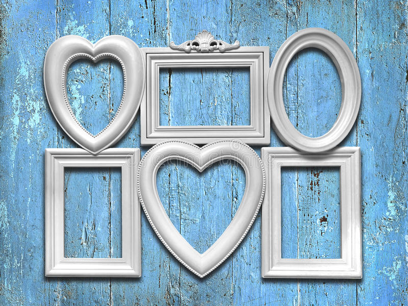 Dekoracyjne białe fotografii ramy na błękitnym drewnianym tle zdjęcie stock
