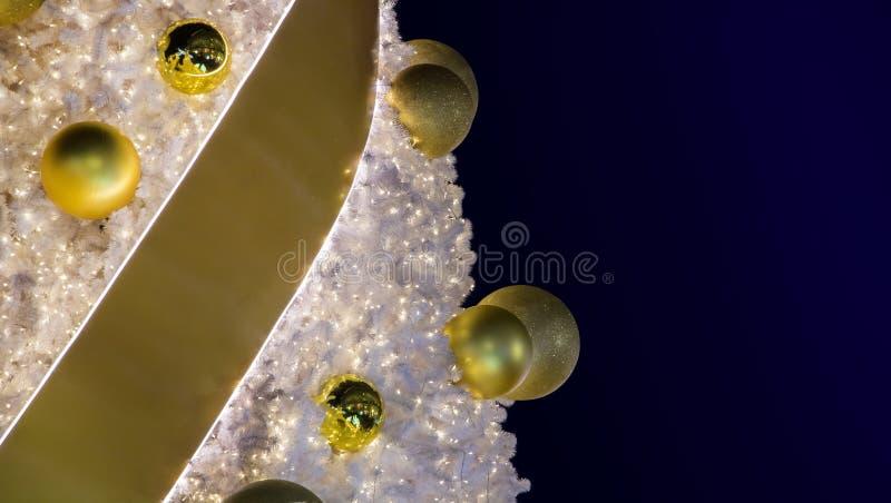 Dekoracyjne złote piłki z tasiemkowym obwieszeniem na choince zdjęcie royalty free