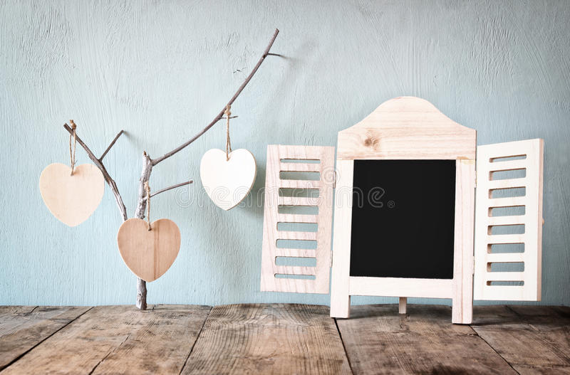 Dekoracyjnego chalkboard ramowi i drewniani wiszący serca nad drewnianym stołem przygotowywający dla teksta lub mockup retro filt obraz stock