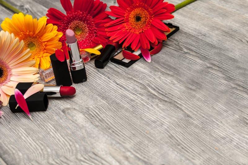 Dekoracyjnego mieszkania nieatutowy skład z produktami, kosmetykami i kwiatami makeup, Mieszkanie nieatutowy, odgórny widok na tl fotografia royalty free