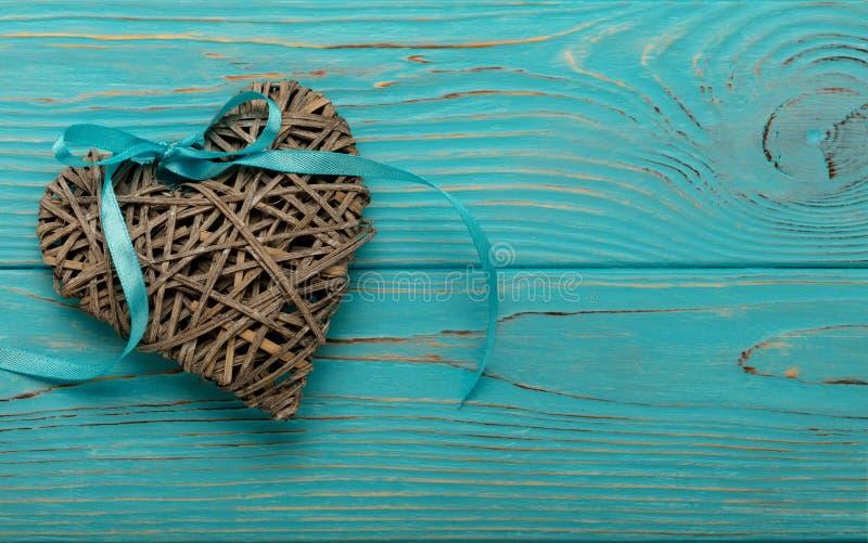 Dekoracyjny łozinowy serce szarość barwi z błękitnym faborkiem na wo obrazy stock