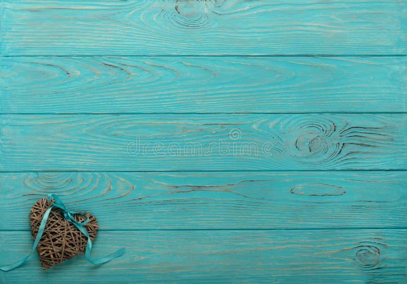 Dekoracyjny łozinowy serce szarość barwi z błękitnym faborkiem na wo obraz royalty free