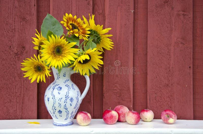Dekoracyjny ceramiczny dzbanka miotacz z słonecznikami i jabłkami obrazy stock