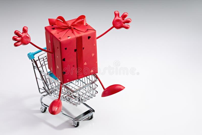 Dekoracyjny czerwony prezenta pudełko z faborkiem w wózku na zakupy fotografia stock
