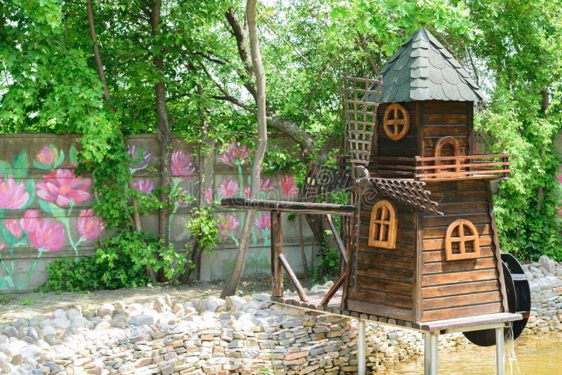 Dekoracyjny drewno wodny i wiatrowy młyn lokalizujący w zieleń parku i kolorowych rysujących kreda kwiatach na betonowej ścianie fotografia royalty free