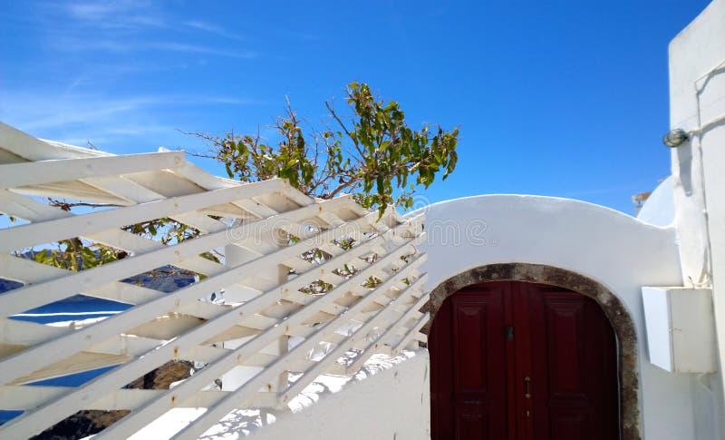 Dekoracyjny ogrodzenie biały kolor przeciw niebieskiemu niebu i jaskrawy Burgundy drzwi w Oia na Santorini obraz stock