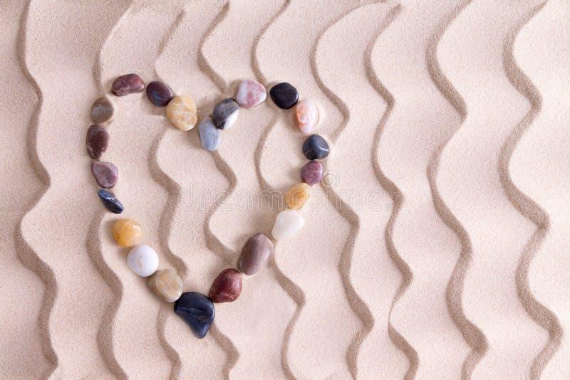 Dekoracyjny otoczaka serce na złotym plażowym piasku zdjęcia royalty free