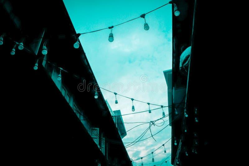 Dekoracyjny plenerowy smyczkowy światło żarówki obwieszenie na elektryczności poczcie w ulicznym noc rynku przy nighttime zdjęcia royalty free