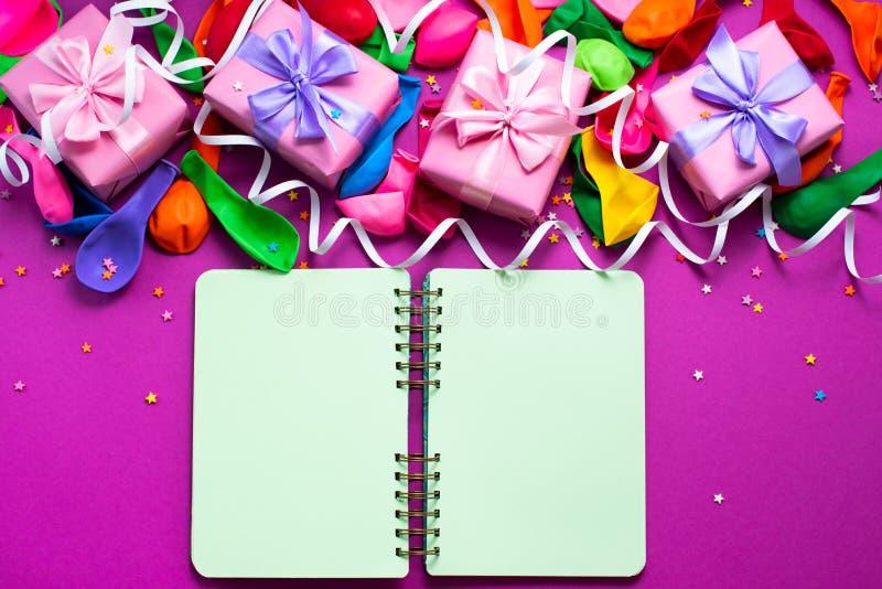 Dekoracyjny pudełkowaty skład z prezenta łęku atłasowych tasiemkowych nadmuchiwanych piłek tła A wężowatym purpurowym odgórnym wi fotografia stock