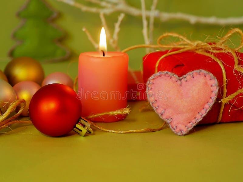 Dekoracyjny sezonowy skład płonąca świeczka, odczuwani serca, choinek piłki, Bożenarodzeniowy wystrój, romantyczny wnętrze zdjęcie stock