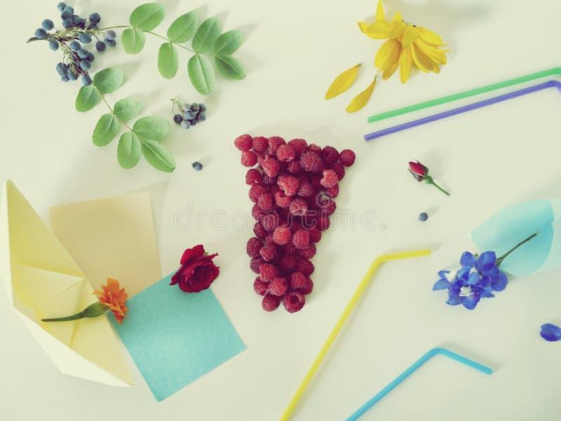 Dekoracyjny skład - szkło świeże malinki, koktajli/lów tubules, świezi kwiaty, płatki i jagody na lekkim tle, zdjęcie royalty free