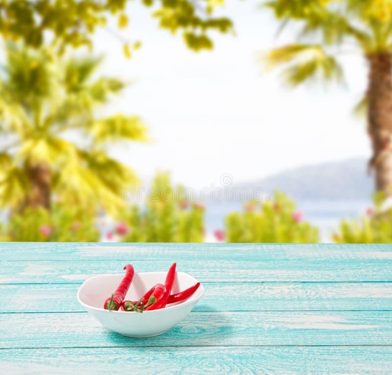 Dekoration des glühenden Paprikapfeffers auf Blau wodden Brett auf unscharfem Strandhintergrund Satz, Kopienraum, Schein oben Cay stockfoto