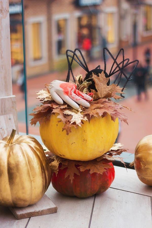 Dekorationen für Halloween Blutige Hand und schwarze Spinne auf einem ora lizenzfreie stockfotos