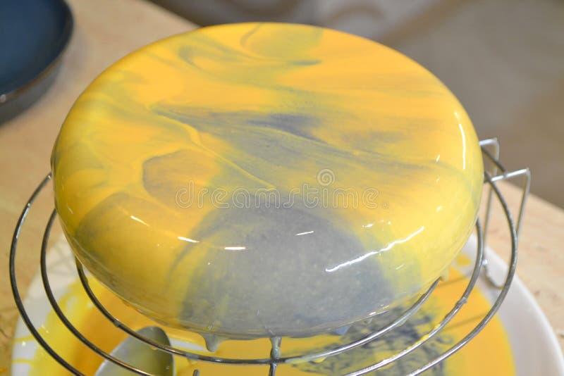 Dekorationsverfahren für Kuchen mit Spiegelverglasung Das Mädchen erstellt eine Zeichnung der Maus auf dem Kuchen Spiegeleisen au stockbild