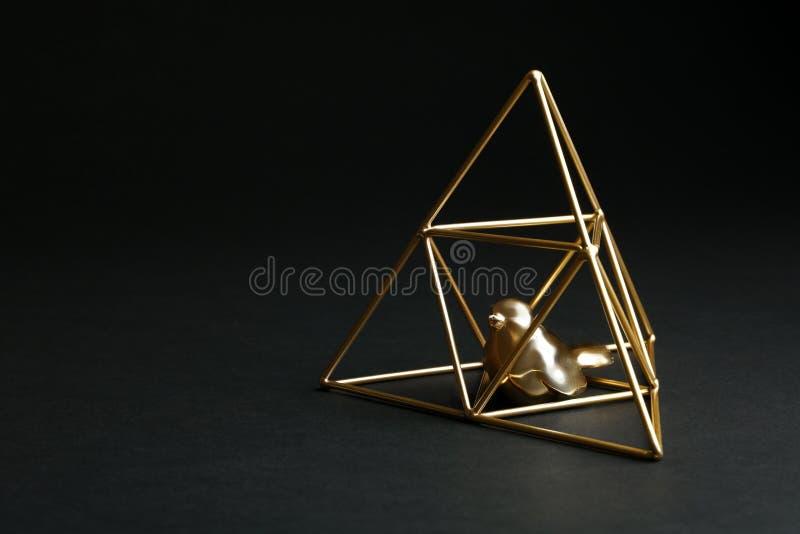 Dekorativ f?gel i guld- pyramid p? svart royaltyfria foton