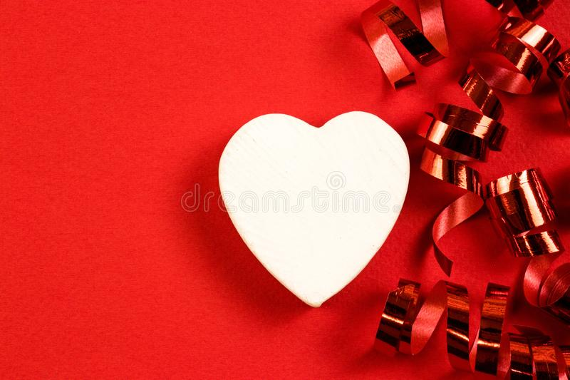 Dekorativ hjärta av en vit färg med röda festliga virvlar på en röd bakgrund kopiera avst?nd royaltyfri bild