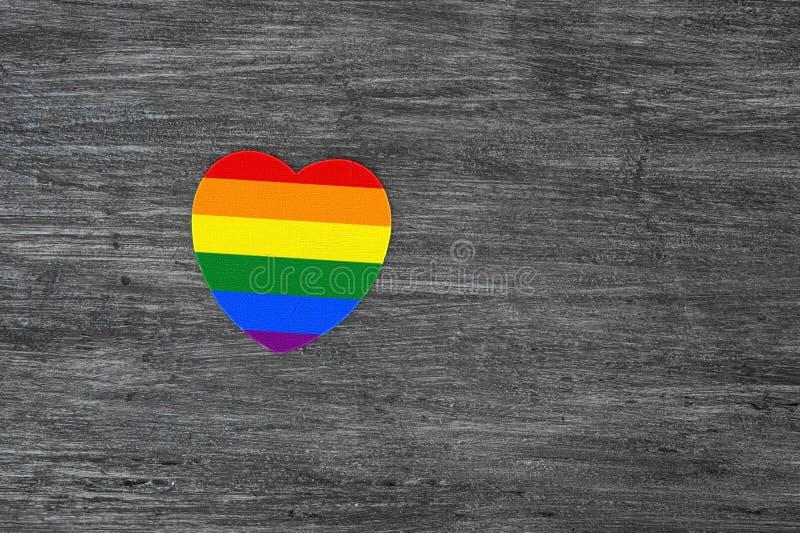 Dekorativ hjärta med regnbågeband på grå träbakgrund LGBT-stolthetflagga, symbol av lesbiskt, glat som är bisexuell, transgender royaltyfri fotografi