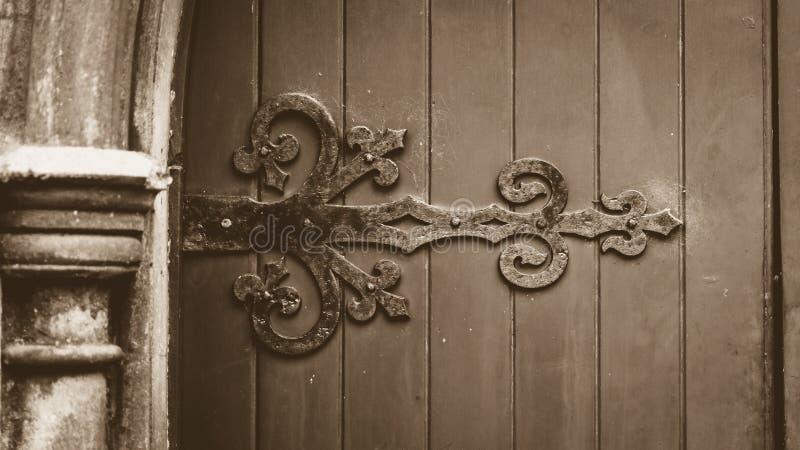 Dekorativ Ironwork på trädörr i Sepiasignal royaltyfri fotografi
