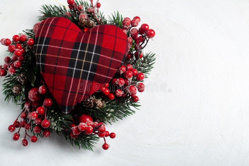 Dekorativ krans för jul av järnek-, murgröna-, mistel-, cederträ- och leylandbladkvistar med röda bär över vit bakgrund fotografering för bildbyråer