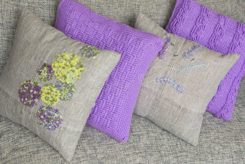Dekorativ kudde som stickas och göras av linnetyg med färgrika - guling, violeten, gräsplan, ljus - blått - broderi arkivfoton