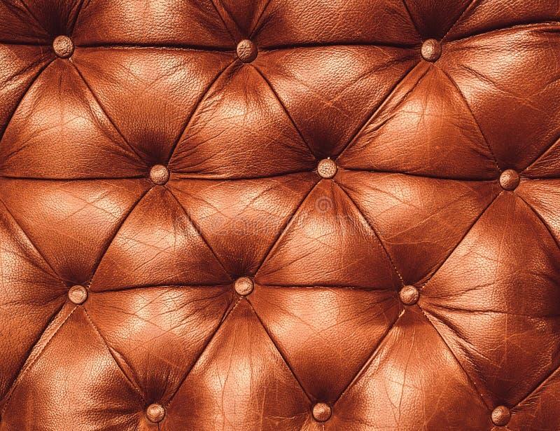 Dekorativ ljust rödbrun bakgrund av äktt läder Dekorativ brun bakgrund av capitonetextur för äktt läder royaltyfria foton