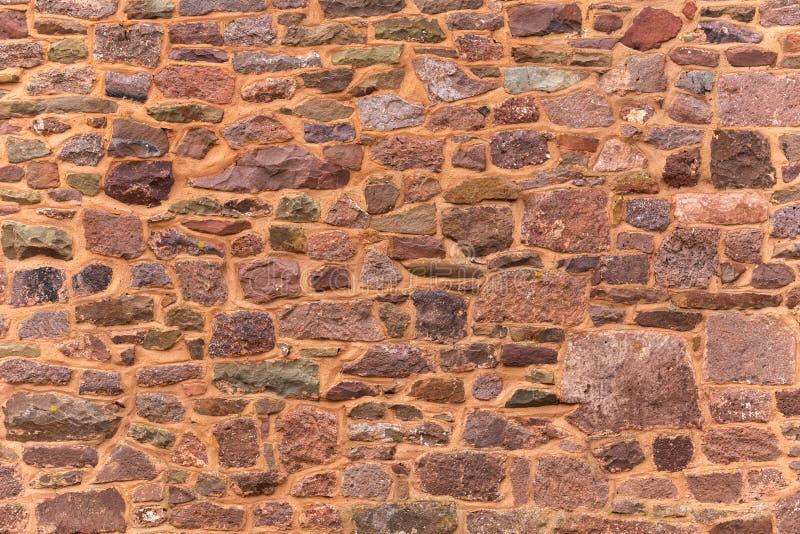 Dekorativ modell av forntida röd bakgrund för stenvägg, textur det slumpmässiga formatet vaggar väggen royaltyfria bilder