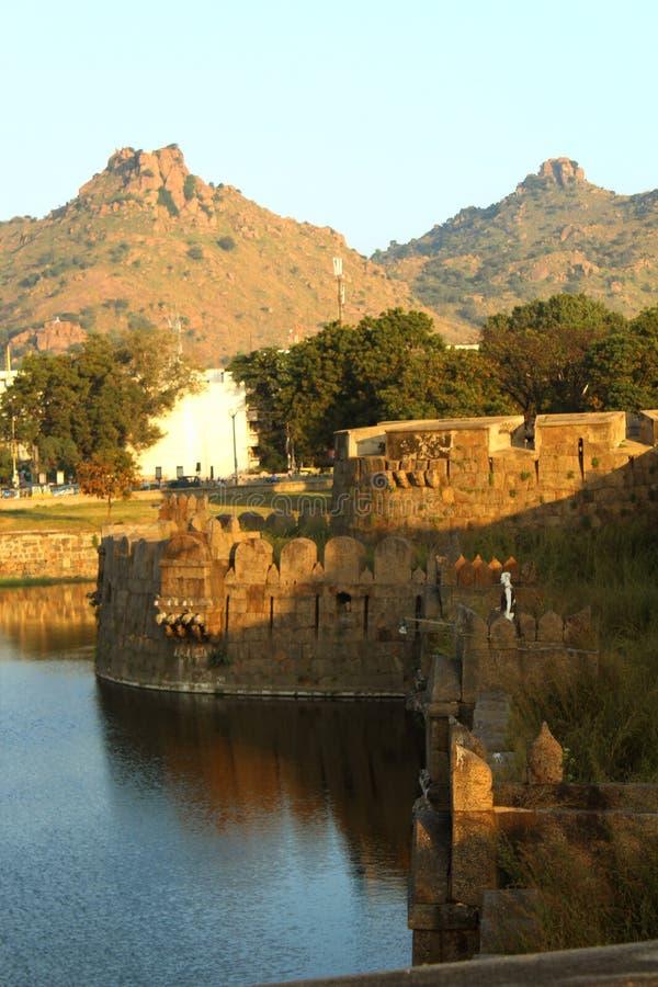 Dekorativ mur med tinnar och dike på vellorefortet med härligt landskap för kullar royaltyfri bild