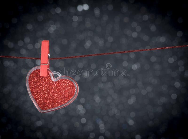 Dekorativ röd hjärta som hänger mot mörk ljus bokehbakgrund, begrepp av valentindagen arkivbild