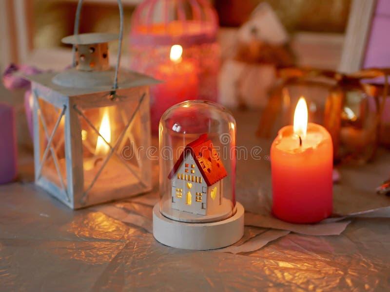 Dekorativ säsongsbetonad sammansättning av brinnande stearinljus, dekorativa lampor, festlig dekor på en silverbakgrund, rosa fär arkivbild