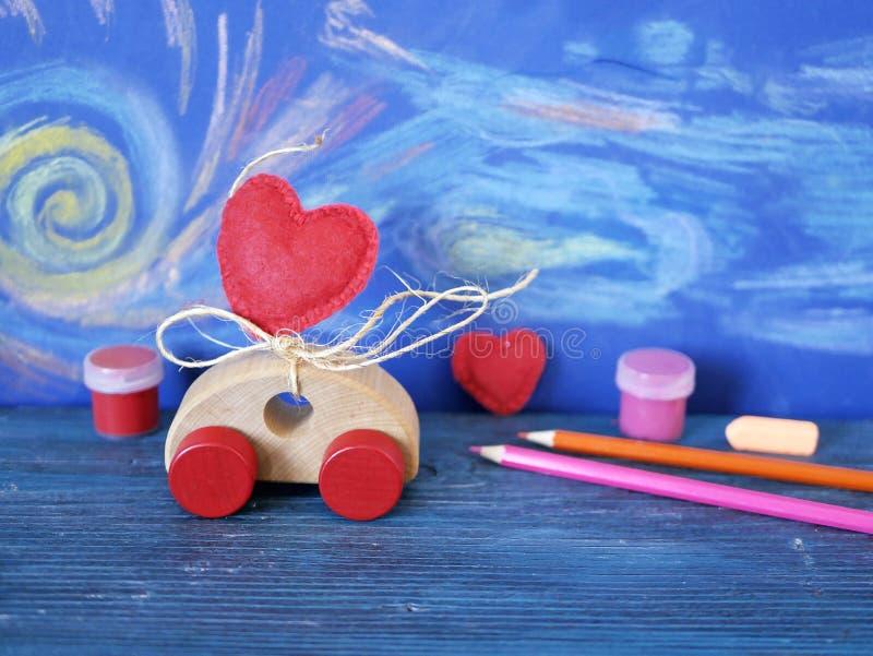 Dekorativ sammansättning av en leksakbil och en hjärta som göras av filt, målarfärger och blyertspennor på bakgrunden av den past royaltyfri foto